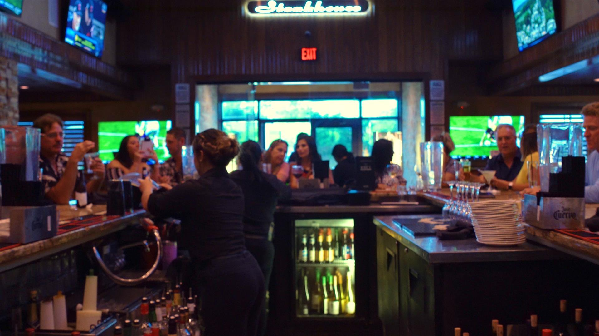 crowded bar filled with patrons and bartenders filling glasses
