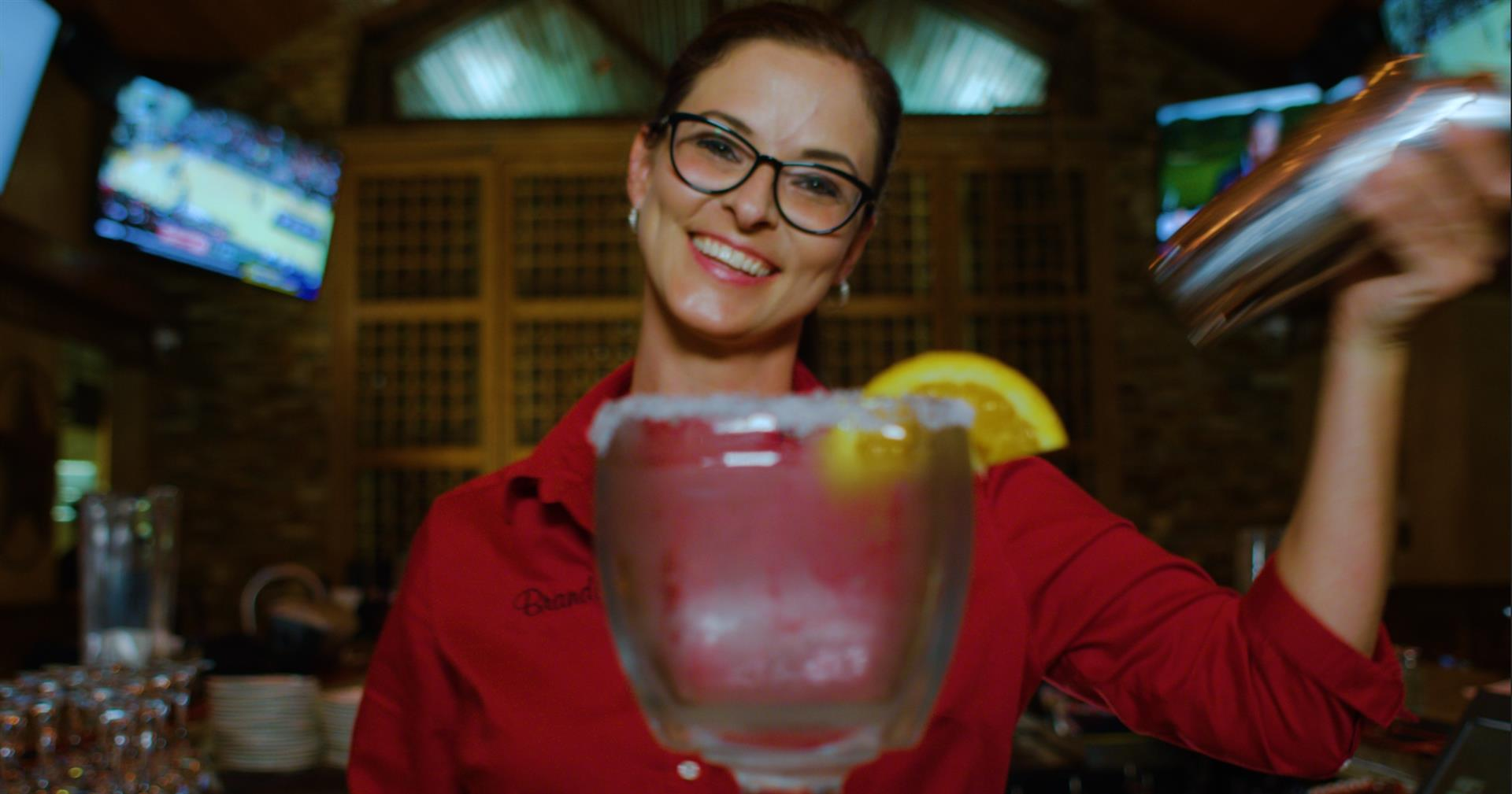waitress smiling while handing over a margarita