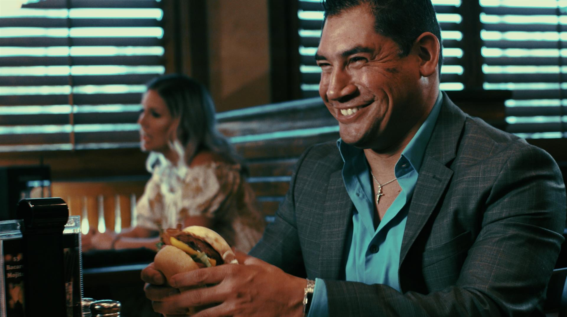 man with a handburger in his hand smiling