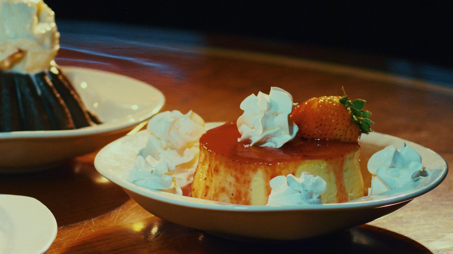flan with strawberry garnish and whipped cream