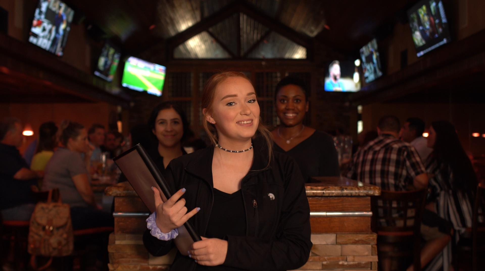 hostess greeting at the door with two other hostess behind her