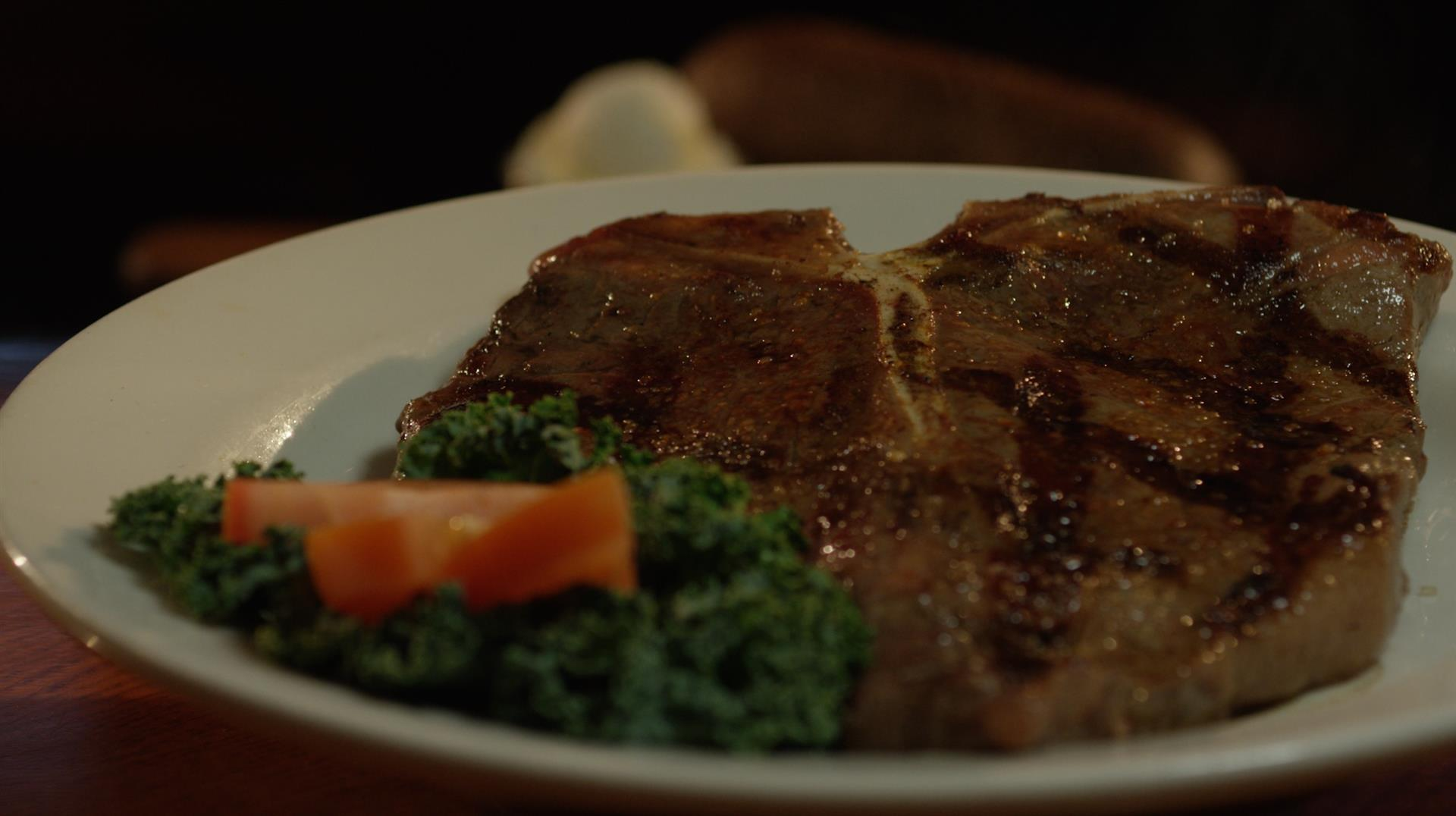 t bone on a plate with an orange garnish