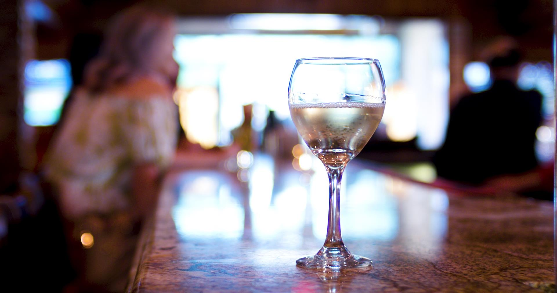 glass of white wine on the bar counter