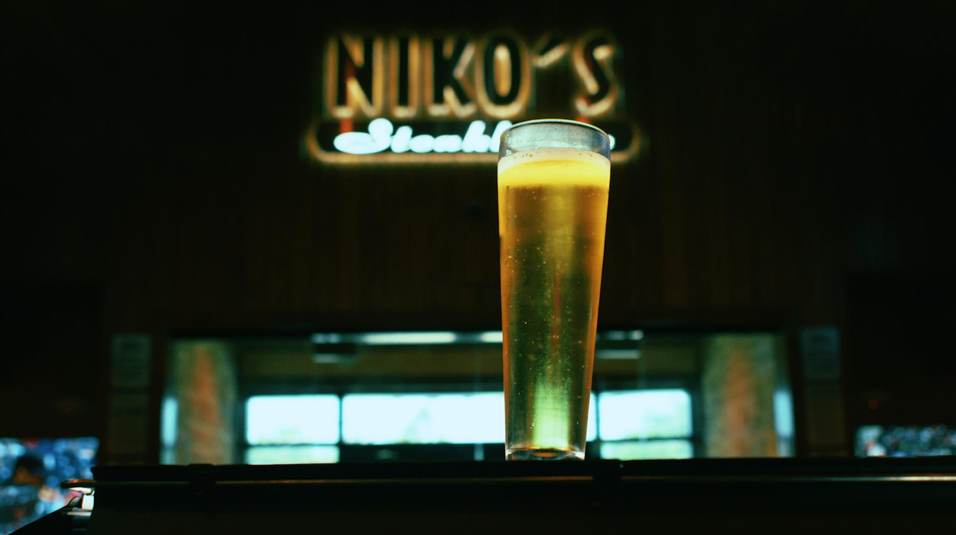 beer glass in front of a blurred, restaurant sign