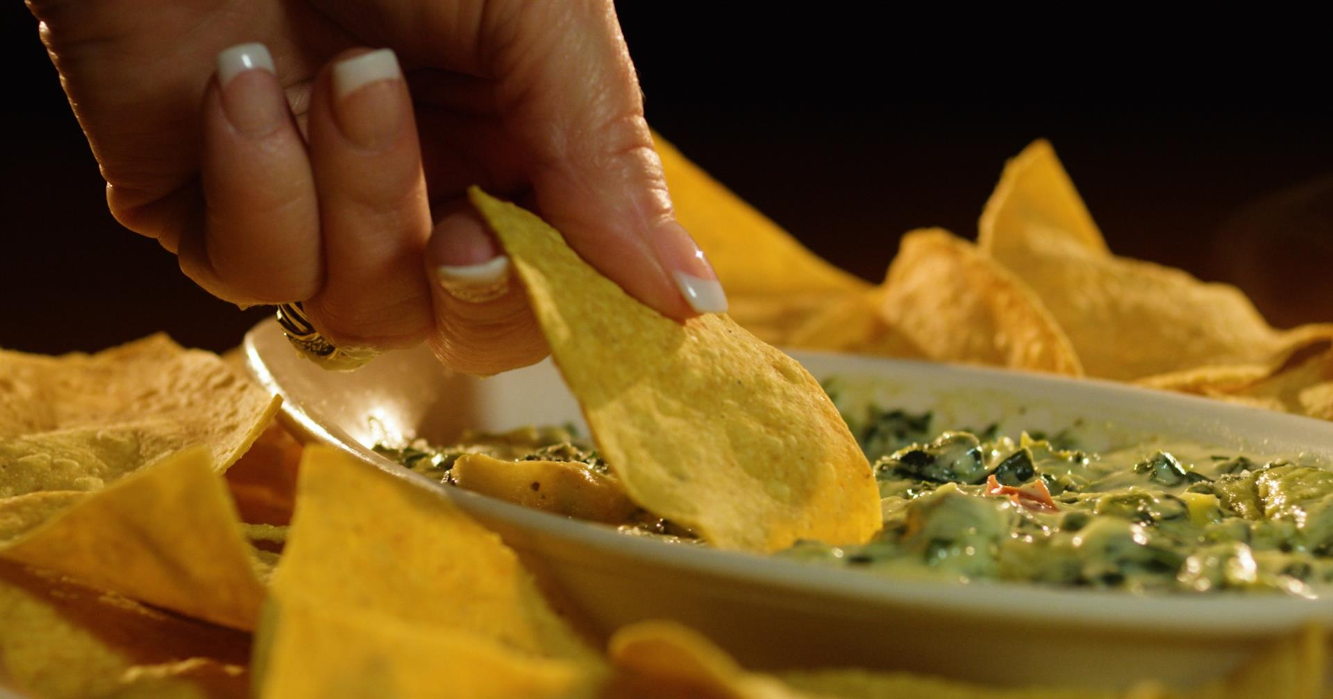spinach and artichoke dip with chips to dip in it