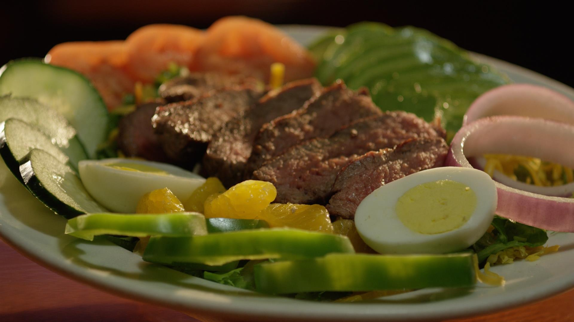 steak salad on a plate with peppers, cucumbers, onions and hard boiled eggs