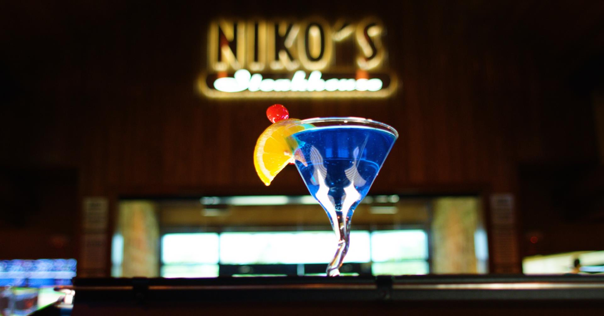 blurred out restaurant sign with a blue martini with a orange and cherry garnish