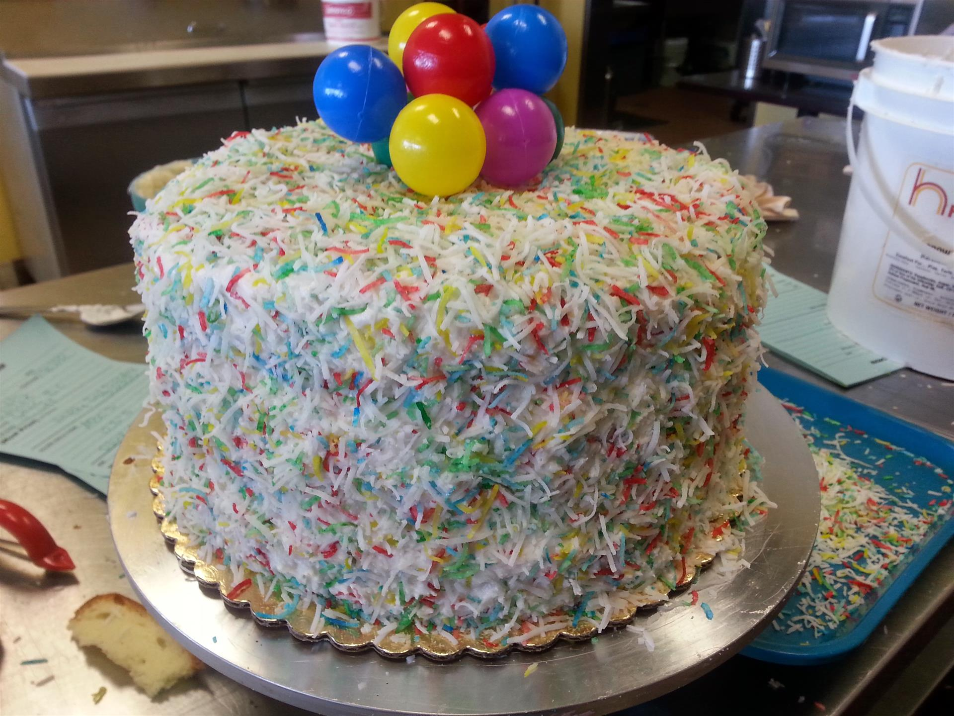 a birthday cake covered in sprinkled and balloons on top