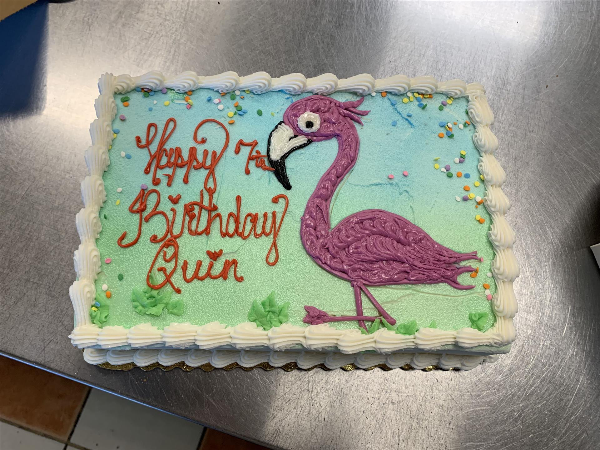 Happy 7th Birthday Quin with a flamingo on top of the cake