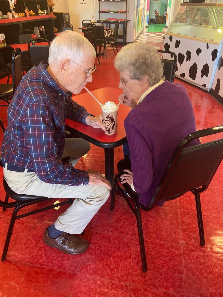 elderly couple drinking a milkshake