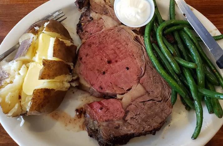 Prime rib with baked potato and string beans