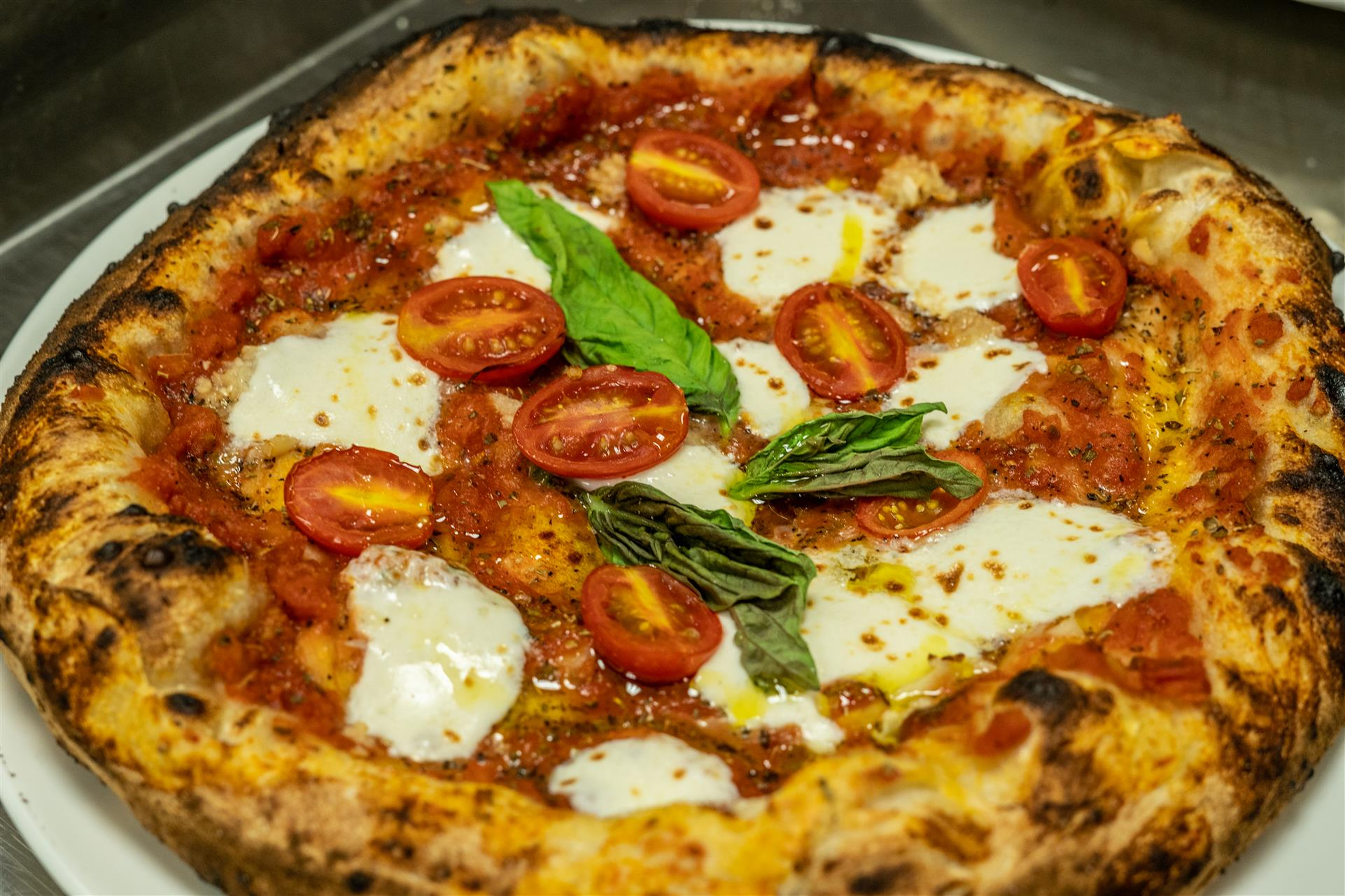 Mario Margarita Pizza. Crushed tomato sauce, fresh Mozzarella di Bufala, blistered cherry tomatoes, basil & olive oil