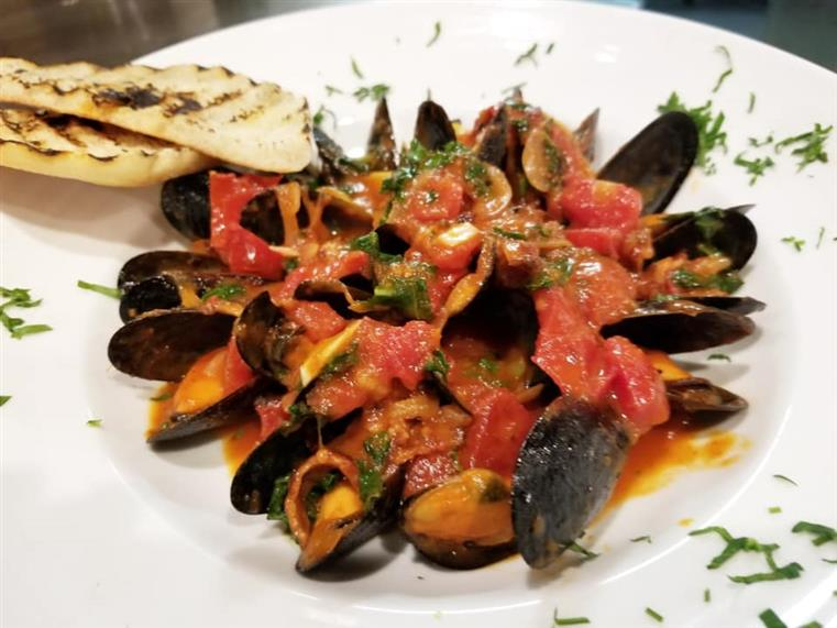 mussels in a red sauce with 2 slices of bread on the side