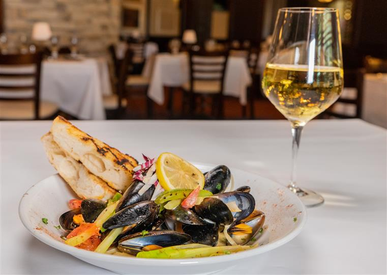 plate with mussels and vegetables on a plate with bread slices and a glass of white wine