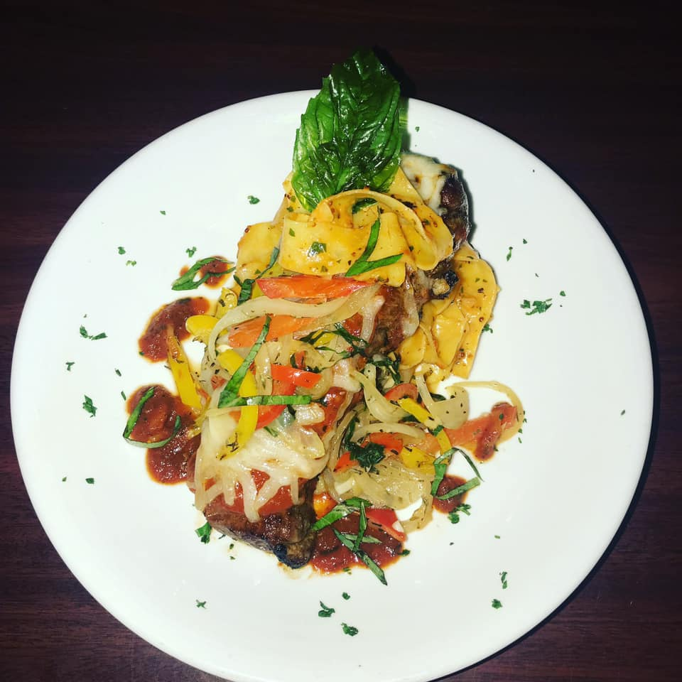 Prime Pizzaiola: A 12 oz. New York strip steak pan-seared with bourbon butter, topped with marinara, Monterey Jack cheese, peppers, onions served over pappardelle pasta with a bourbon butter basil sauce.
