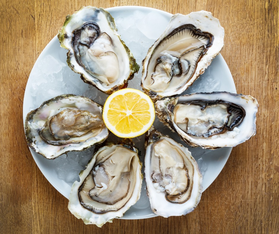oysters surrounding a half of a lemon on a plate