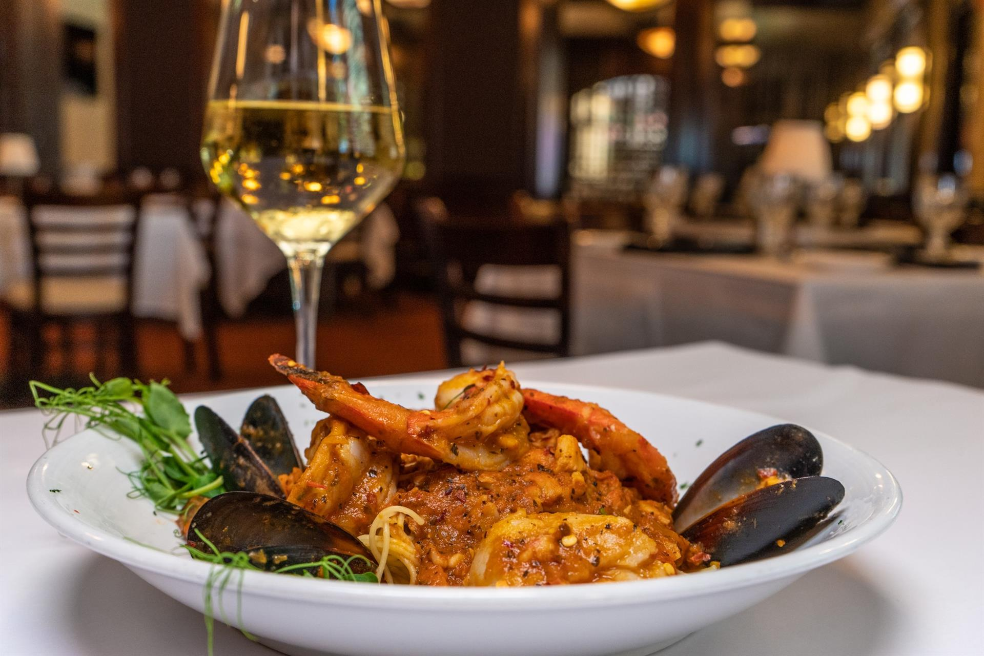 shrimp and mussels in a plate with a glass of white wine