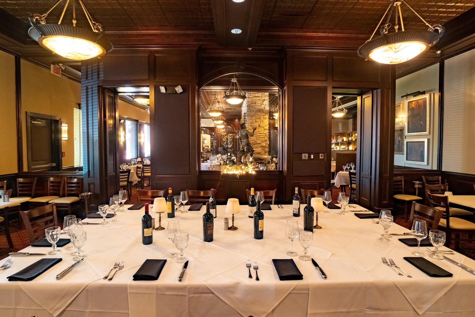 inside the restaurant, in the wine room, photo of a set table with wine bottles and place settings