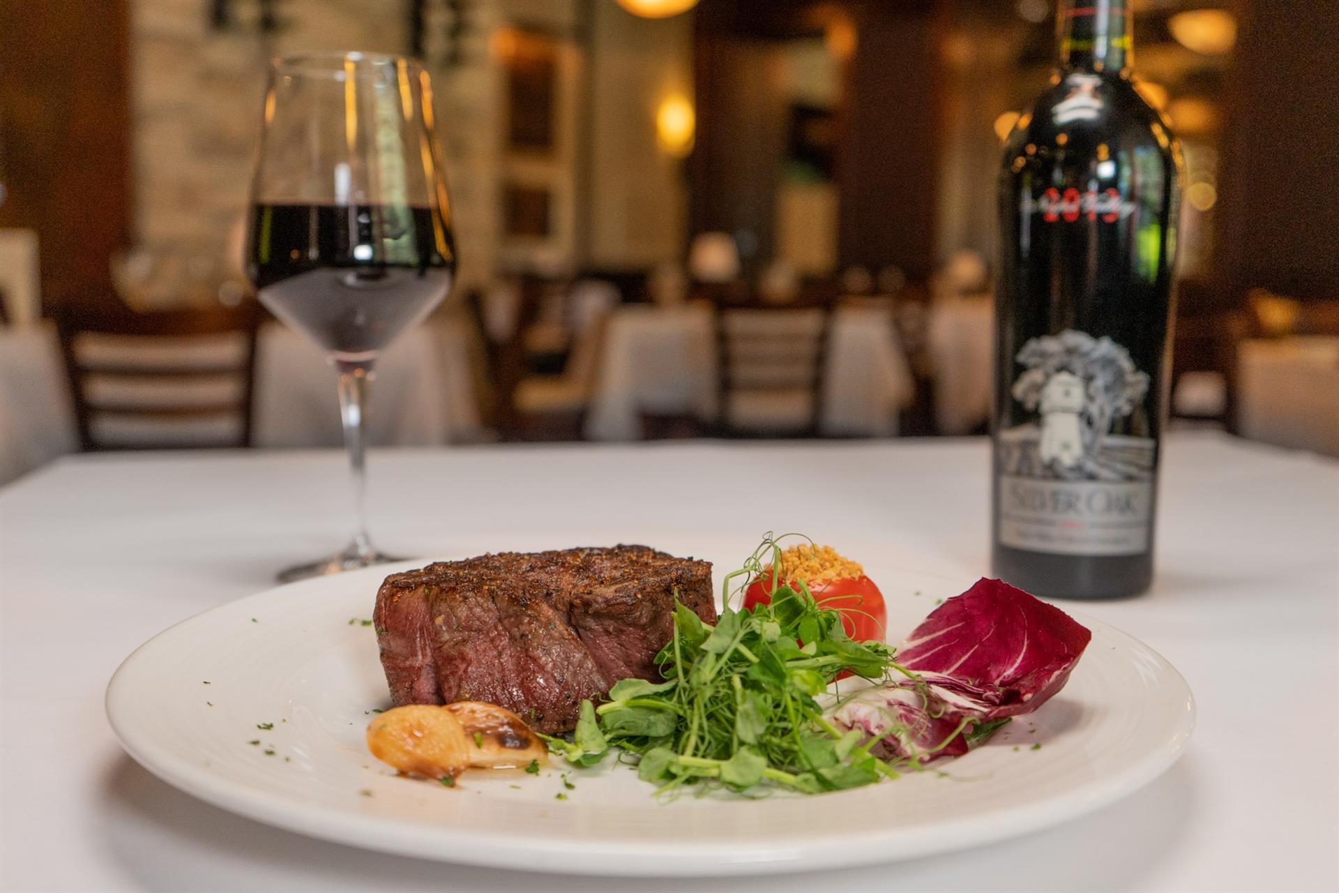8 ounce Petit Filet Mignon with small salad and a glass of red wine on a table.