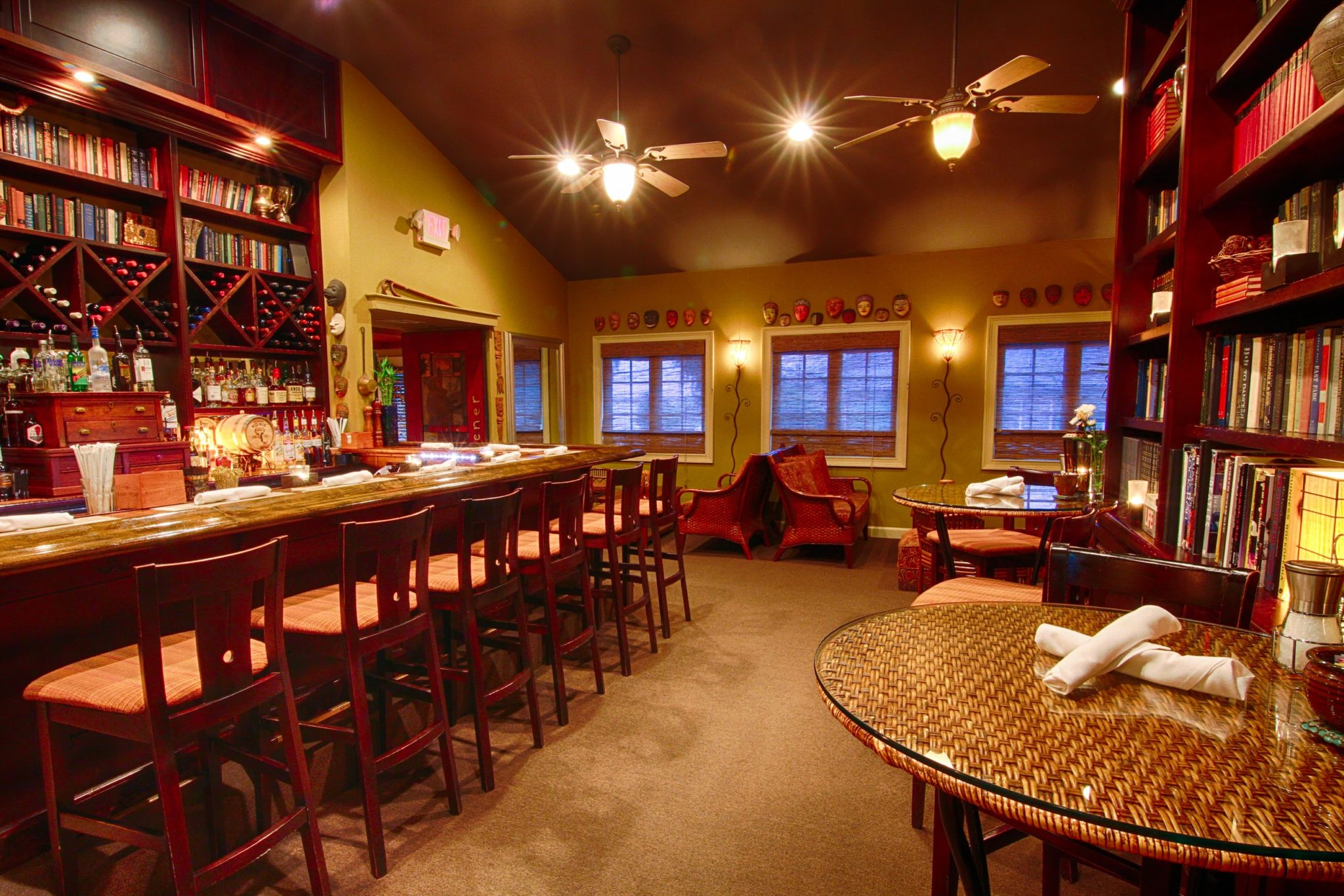 Bar countertop with high-top chairs and a bookshelf wall behind the bar.