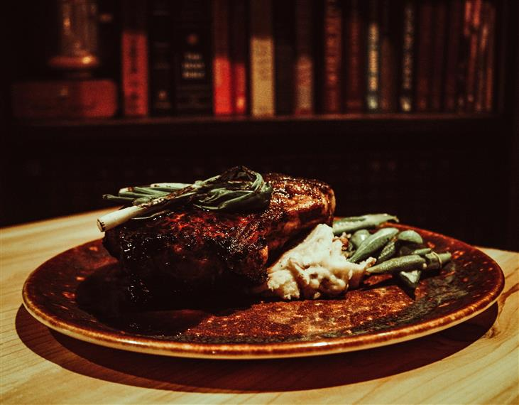 ancho dusted pan-seared carolina bone-in chop with milk stout demi & charred scallion over mashed potatoes, with a side of green beans