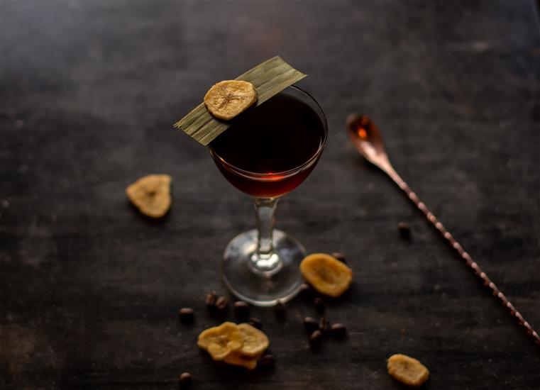 A cocktail surrounded by sliced banana and a bar spoon.