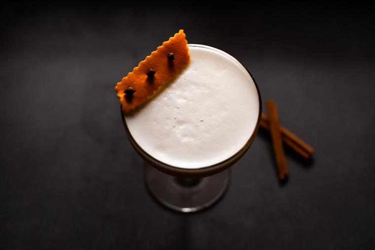 A lovely cocktail with orange zest and egg white foam.