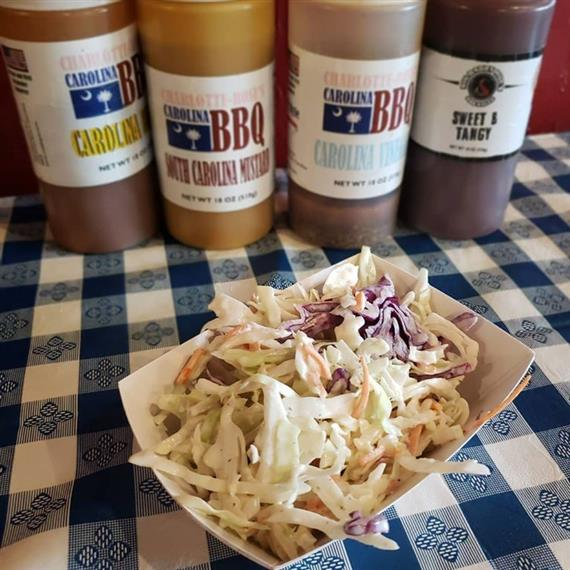 homemade coleslaw on a table next to bottles of charlotte rose's carolina bbq sauces