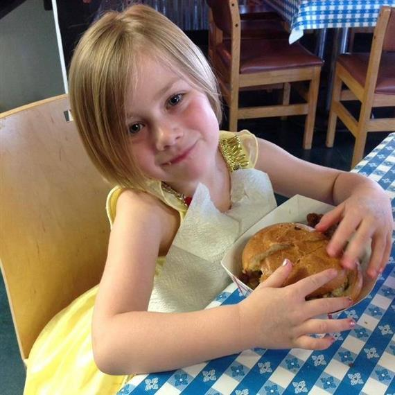 Charlotte Rose holding a bbq sandwich inside the restaurant