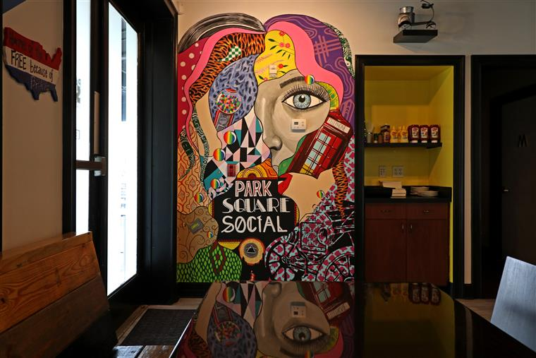"A wall painted with abstract figured that says ""Park Square Social"""
