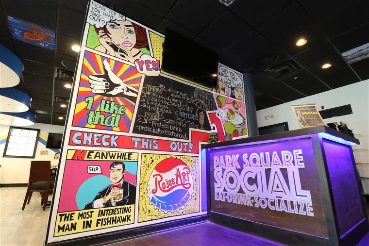 The front counter of Park Square Social with a wall painted in comic art