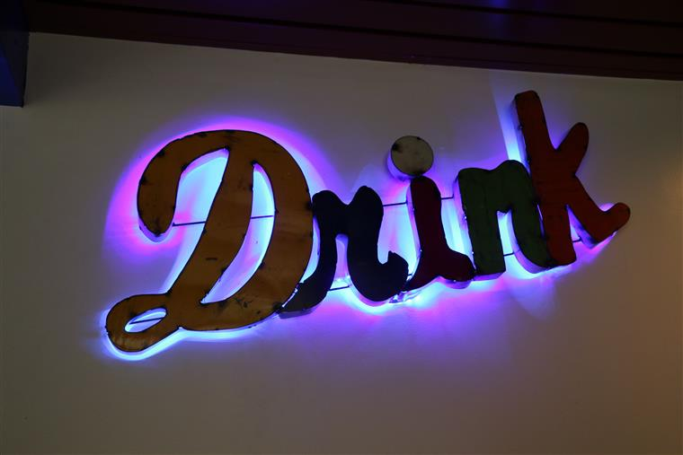 "A neon light up sign that says ""Drink"""