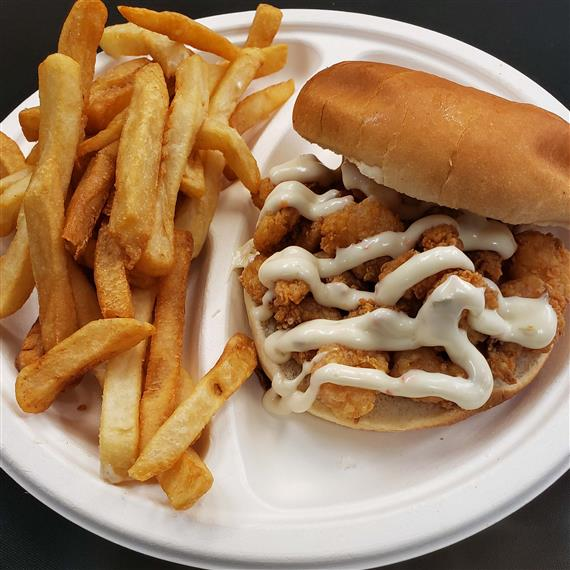 A fried fish sandwich topped with tartar sauce and French fries on the side