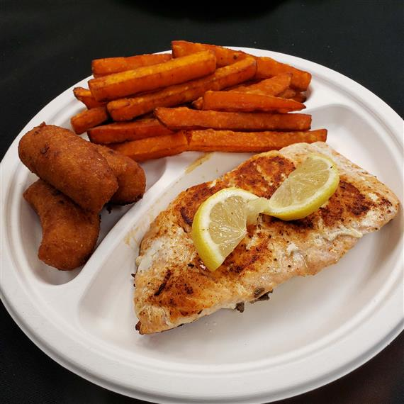 Grilled Flounder, topped with two lemon wedges with a side of sweet potato fries.
