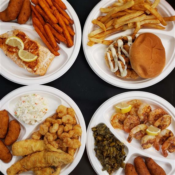 4 plates of fried fish with sides of French fries, sweet potato fries, spinach, and coleslaw