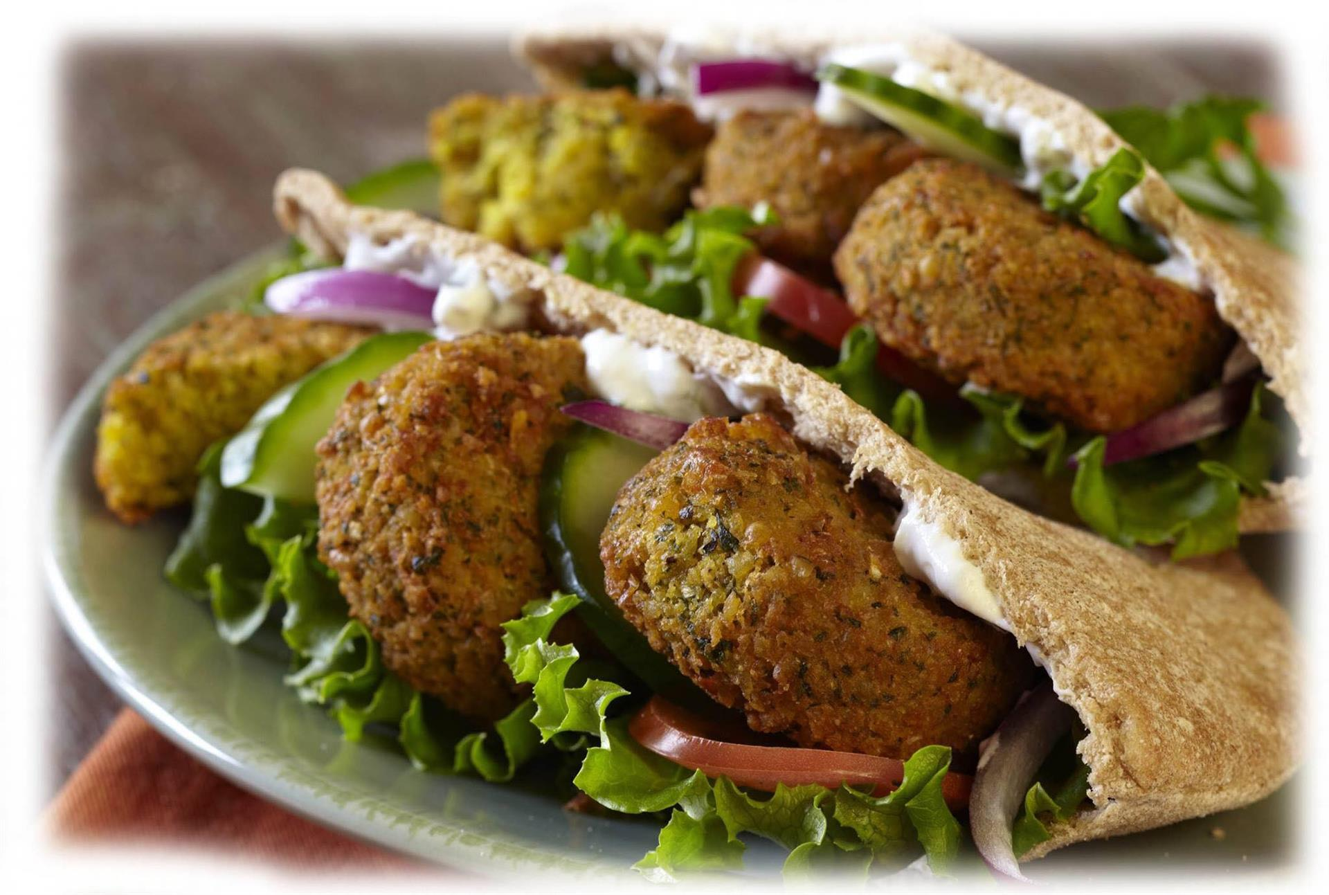 Two pita pockets stuffed with falafels, lettuce, tomato, onion and cucumbers.