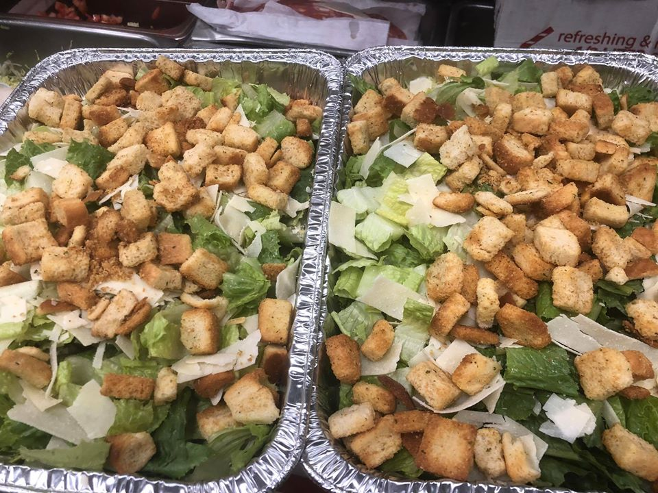 two large trays of caesar salads.
