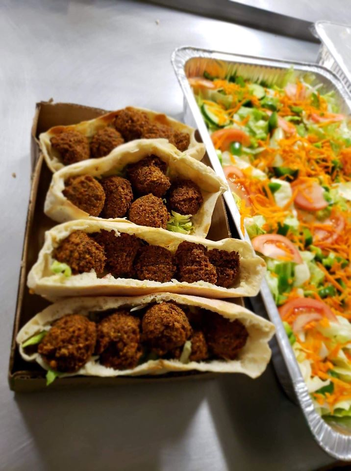 four pita pockets stuffed with falafel with salad on the side.