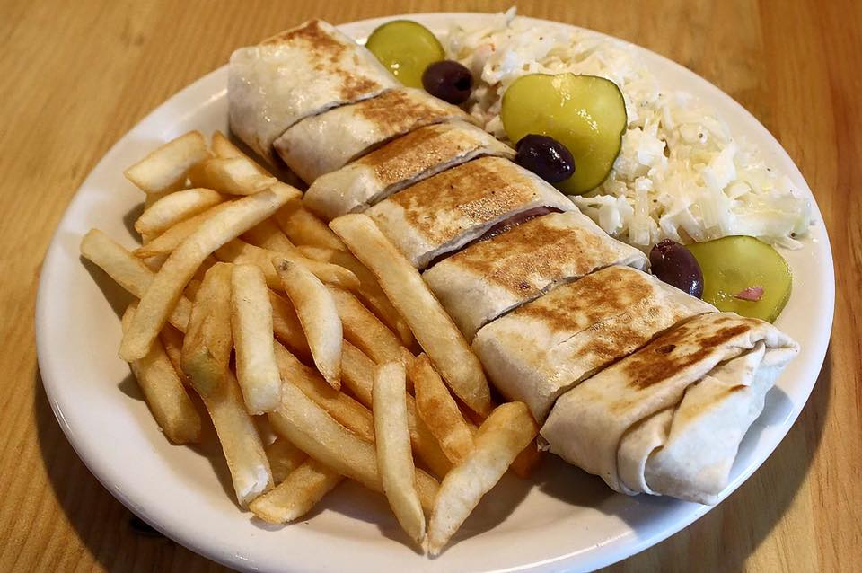 gyro sliced up with a side of handcut fries, and pickles with olives
