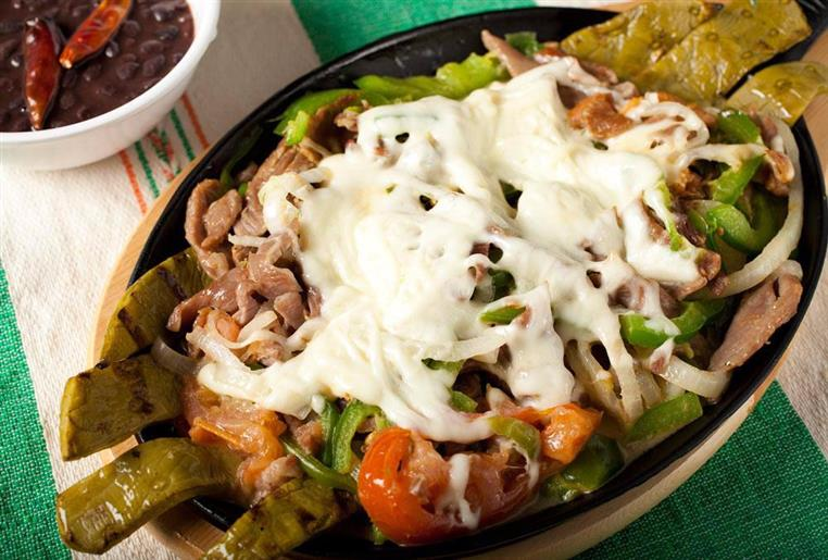 pork fajitas  in a skillet topped with peppers, onions and melted cheese