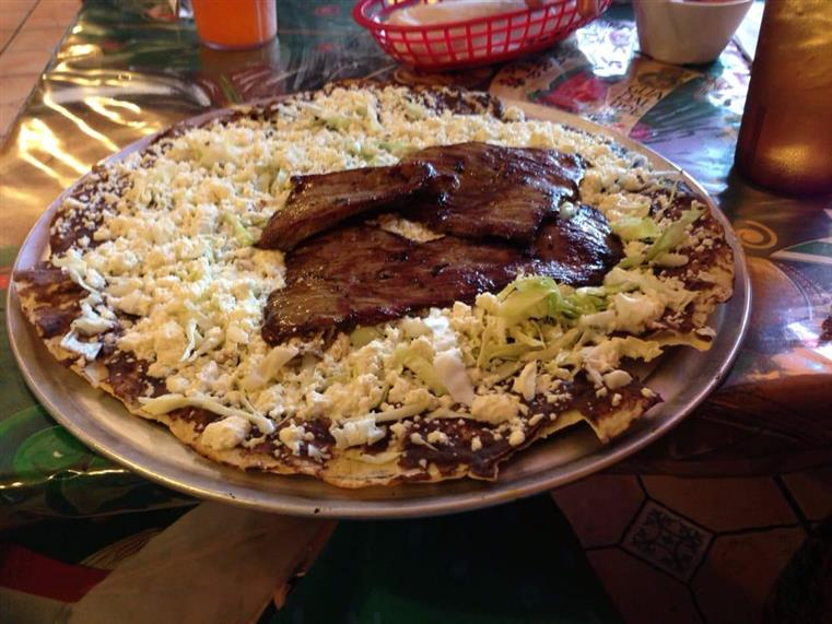 large tostada plate topped with shredded lettuce, cheese, tomatoes, and various types of meat