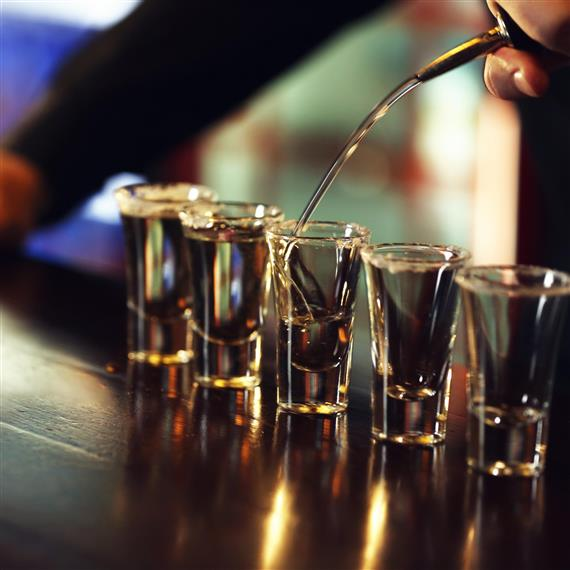Bartender pouring liquor into shot glasses