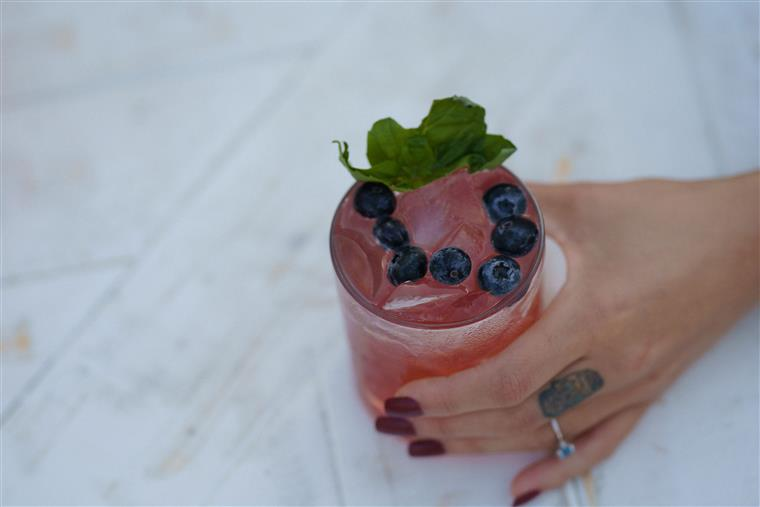 A berry vodka drink topped with mint leaves and blueberries