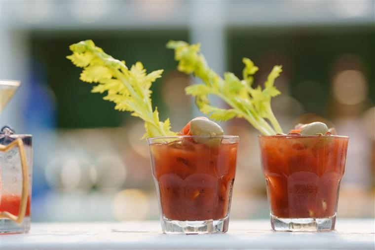 2 bloody Marys on a bar top, garnished with leafy greens and olives