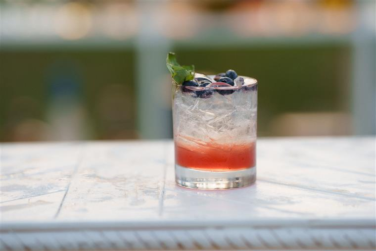 A berry vodka soda topped with fresh blueberries and mint leaves