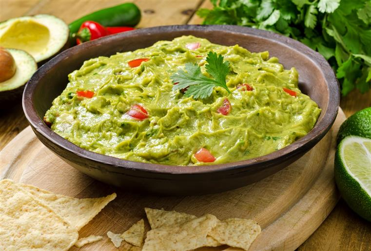 Guacamole with avocado, lime, tomato, and cilantro with tortilla chips