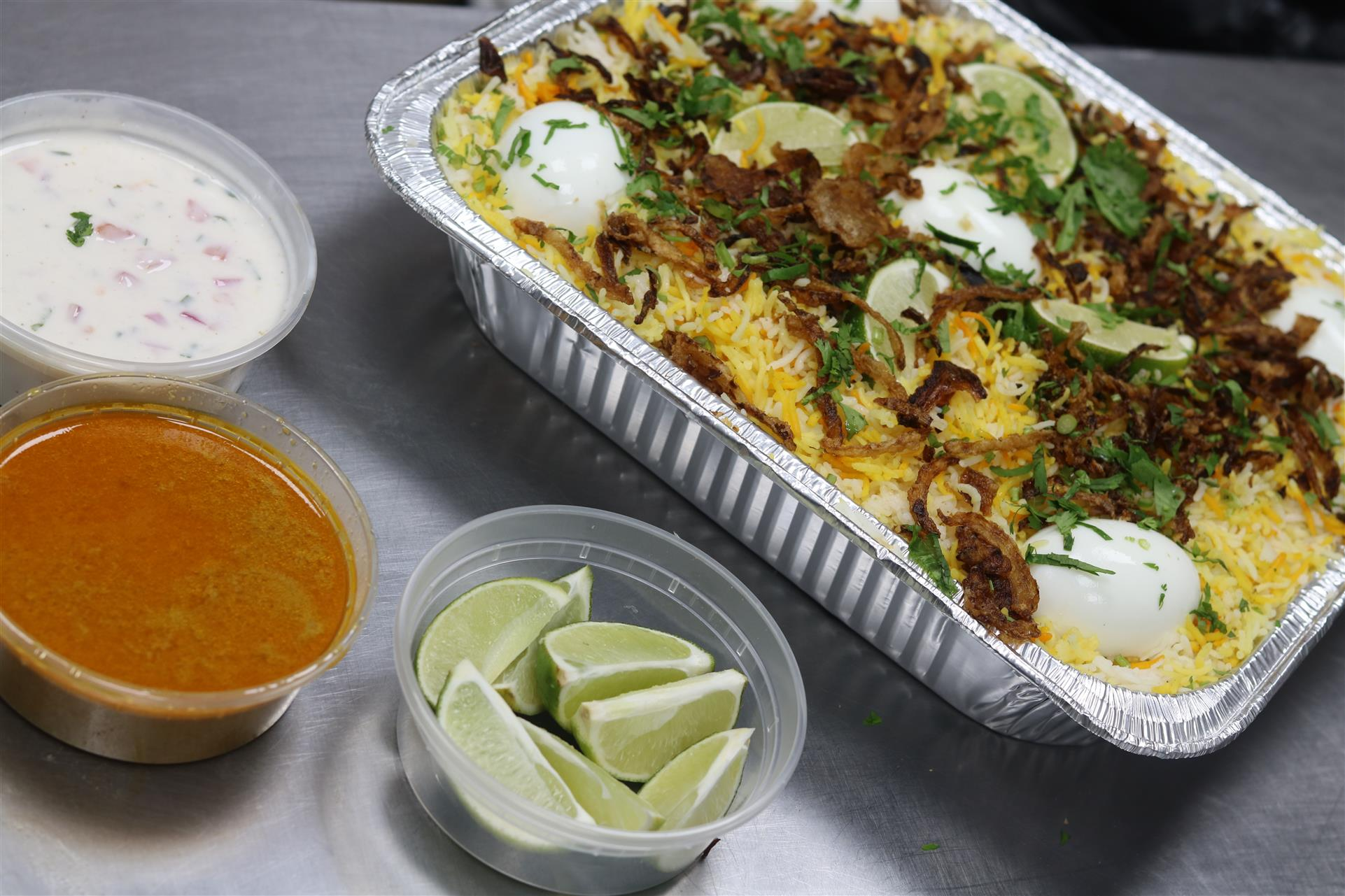 biryani tray with sauces and limes