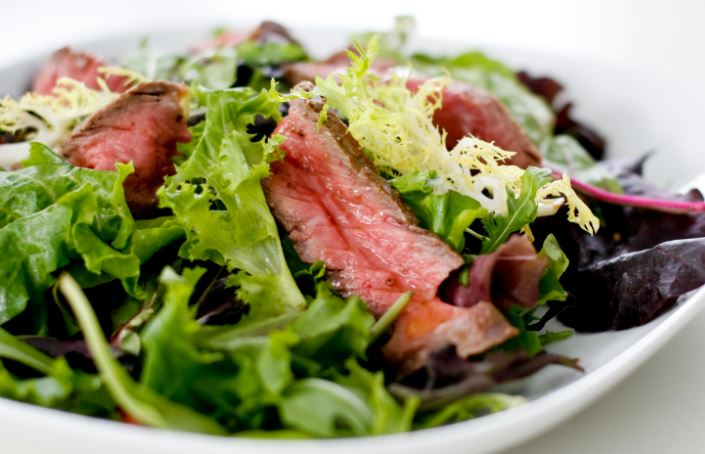 A steak salad with mixed greens