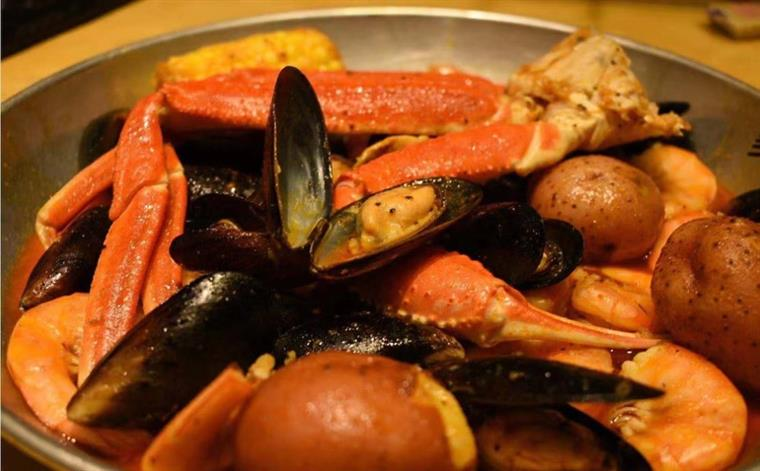 mussels, corn, potatoes, and crab legs in a bowl with sauce