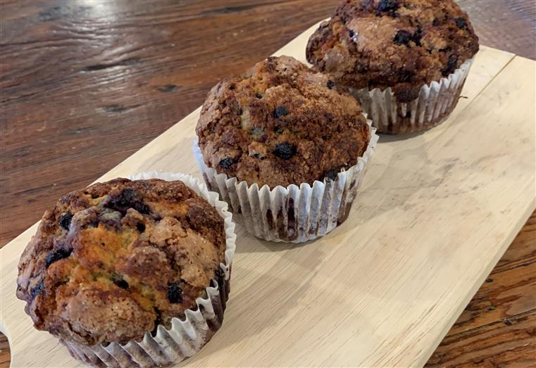 three chocolate chip muffins on a wood table.